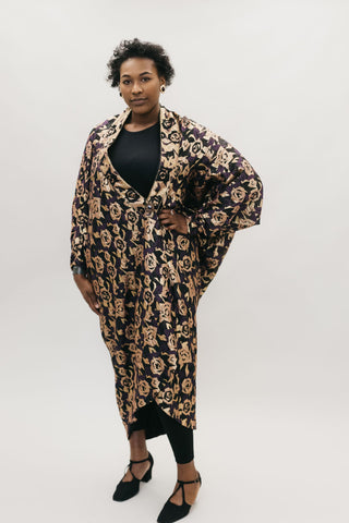 African American woman standing with left hand on her hipin front of a studio white backdrop wearing the 503 Poiret Cocoon Coat in a silk charmeuse fabric with gold roses as the pattern. She is also wearing black closed toed shoes.
