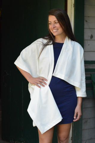 Burnett white woman with her right hand on her hip wearing a navy blue fitted dress underneath a white #271 Sunset Wrap that is draped over her shoulders.