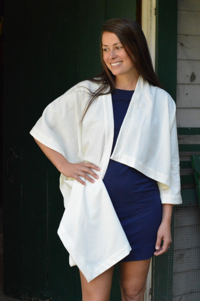 brunette  white woman with her right hand on her hip wearing a navy blue fitted dress underneath a white #271 Sunset Wrap that is draped over her shoulders.