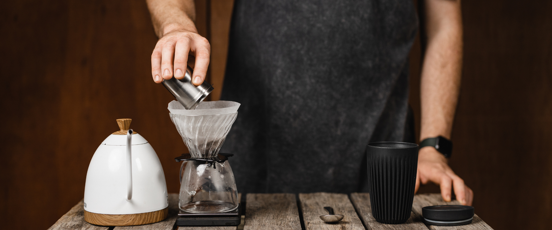 Person placing coffee grinds into v60 hario dripper