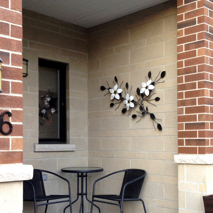 Metal Flower Vine wall-mounted in the alcove of a building hanging above two chairs and a patio table: 3 large white flowers on an ornamental vine with hand-eetched leaves