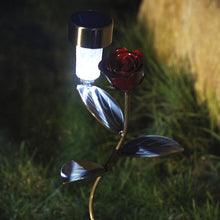 Red Rose Solar Light On A Garden Stake = Made By Practical Art: LED light is on casting light on the detailed metal rose flower on a metal vine with hand-etched leaves and the brown and green colours / colour of a garden are blurred in the backdrop to accent the metal art on a garden stake product..