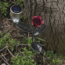 Red Rose Solar Light On A Garden Stake = Metal Art By Practical Art: LED light is off during daytime aerial view of this red metal flower with Led Light attached and that is planted amidst green plants beside a big oak tree.