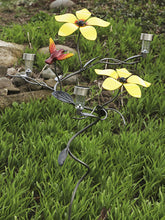 2 Large Yellow Metal Flowers and an attached red and yellow hummingbird with 3 solar lights on a wrought iron vine that has hand-etched leaves on a garden stake planted in a garden amidst lush green plants during the daytime.