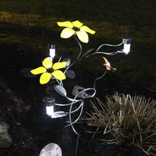 2 Large Yellow Metal Flowers and an attached red and yellow hummingbird with 3 solar lights alight on a wrought iron vine that has hand-etched leaves on a garden stake planted in a garden beside a plant during night-time darkness.
