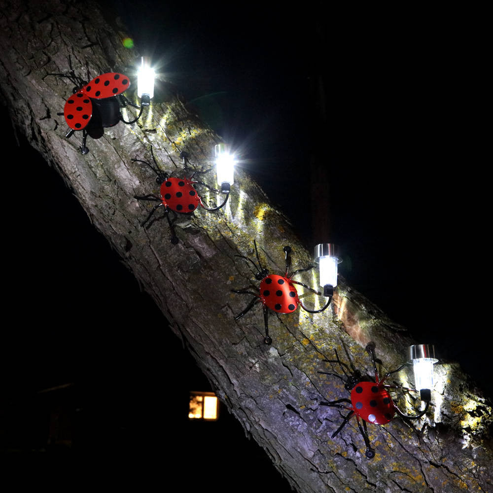 Ladybug Family: 4 Metal Ladybugs each with a solar-light alit climbing up a tree trunk in the dark: 2 Large Ladybugs and 2 small ones