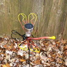 Metal Dragonfly On A Garden Stake With Solar Light Profile View In Front Of A Wooden Fence And Autumn Leaves On The Ground