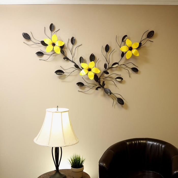 Metal Flower Vine Wall Art hanging as interior wall décor above  a large arm chair and an end  table with a lit lamp : 3 large bright yellow flowers on an ornamental vine with hand-eetched leaves