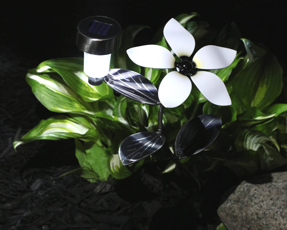White Metal Flower with ornamental vine that has hand-etched leaves and an attached solar light alit planted in a garden beside a plant during night-time darkness.