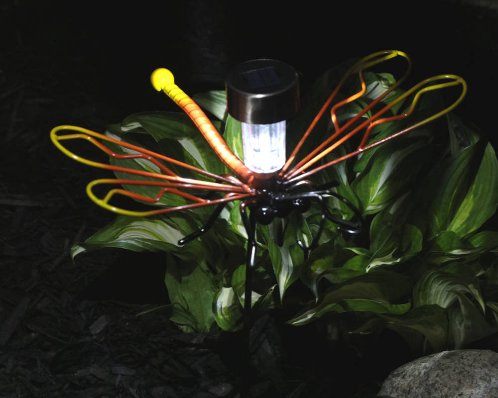 Metal Dragonfly On A Garden Stake With Solar Light Alight And Planted In A Garden With A Bright Green Plant In The Background.