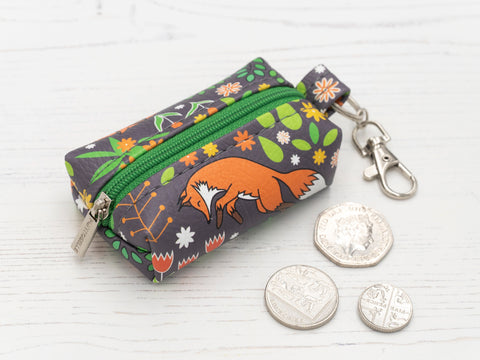 Punto Belle coin purse with fox pattern with coins on a desk