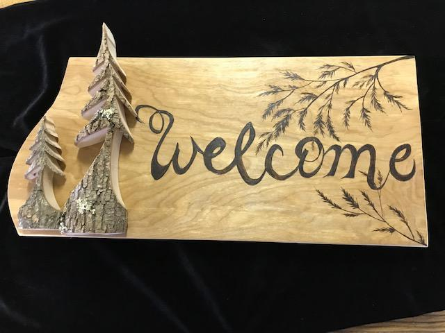 Welcome sign with 2 trees