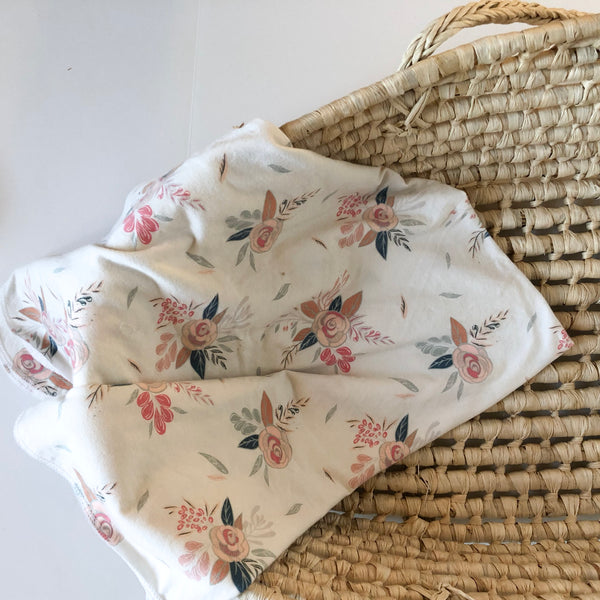 pink-white-flower-print-handmade-swaddle-blanket-for-babies-hanging-over-side-of-moses-basket