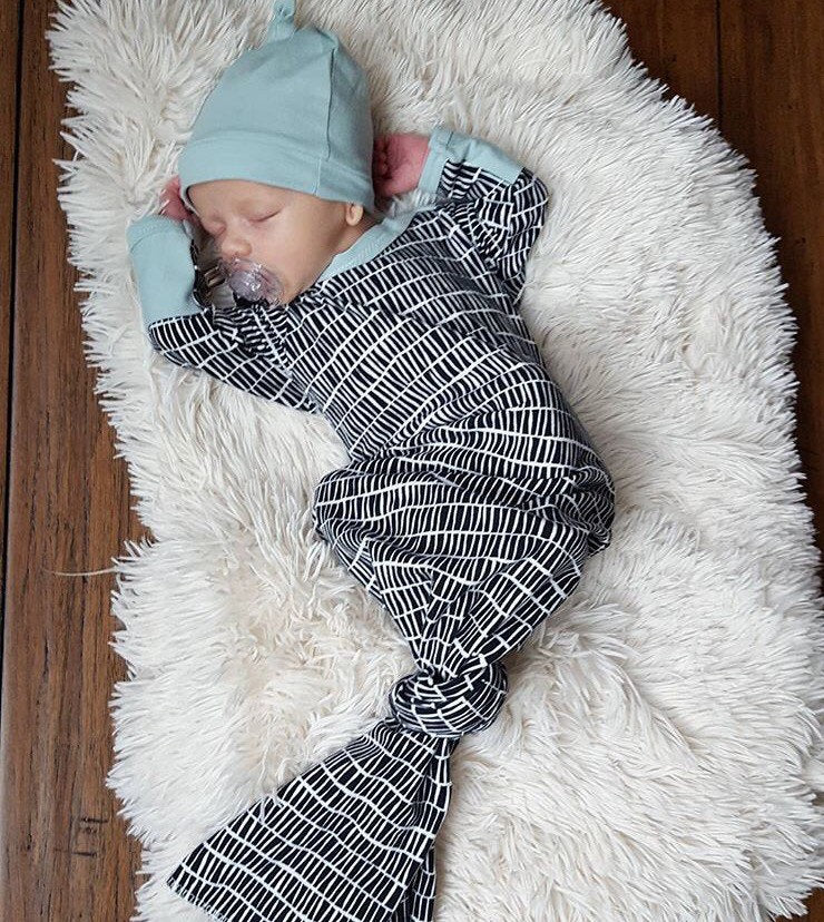 baby-sleeping-in-black-and-white-newborn-knotted-gown-hat-coming-home-outfit