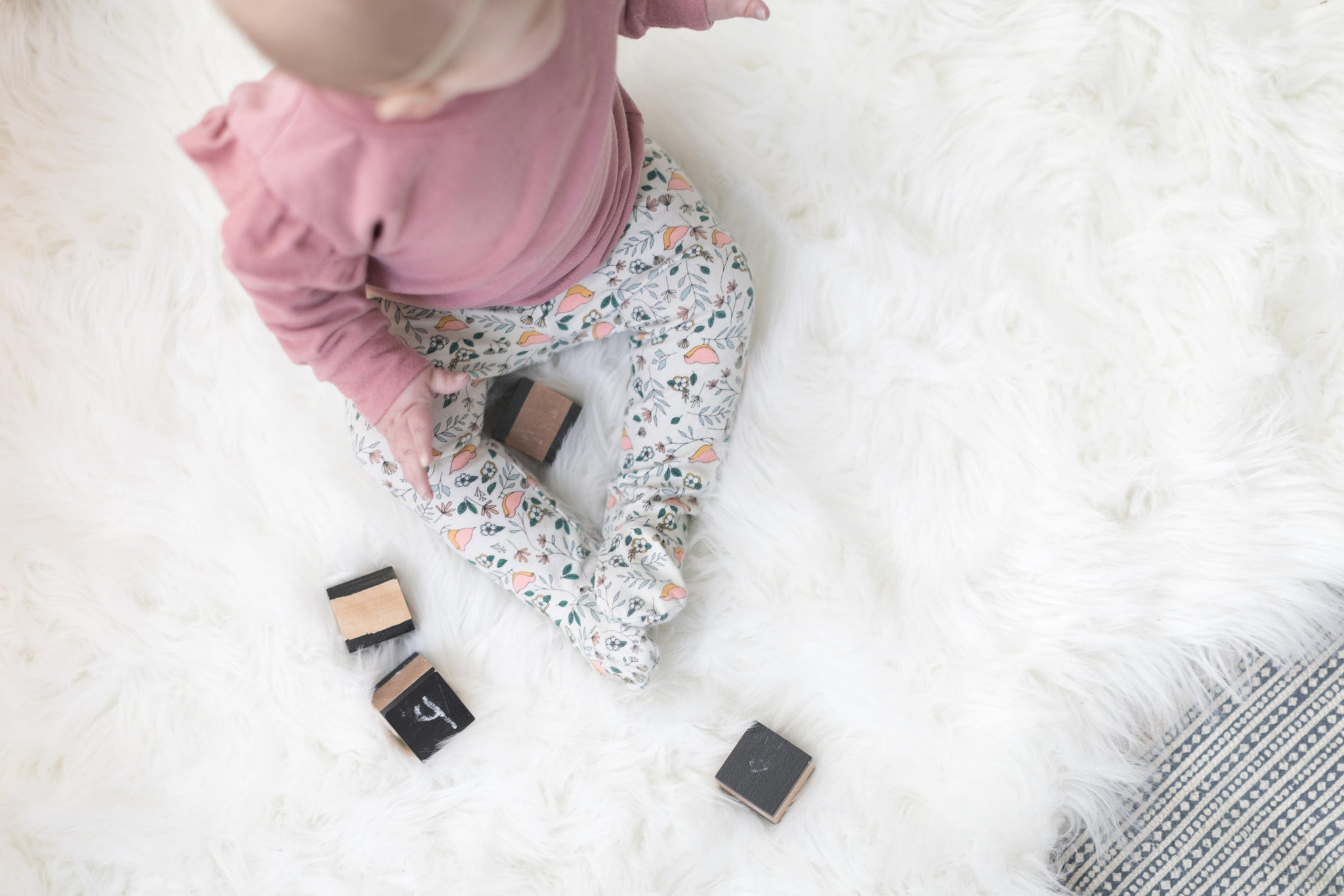 baby-girl-playing-with-blocks-wearing-pink-sweater-and-handmade-floral-footed-pants