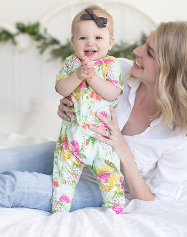 baby-girl-standing-in-pink-green-gold-romper-smiling-with-mommy