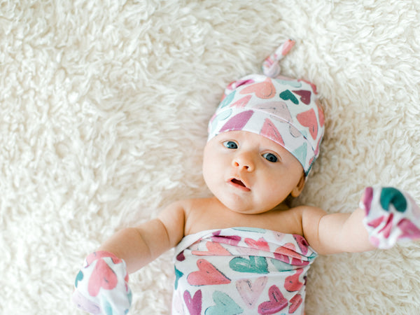 baby-girl-wearing-heart-hat-swaddle-blanket-mittens-sweetest-newborn-photo-props