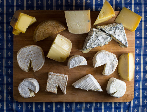 a wide variety of cheeses on a wooden board