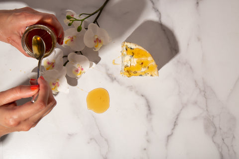 drizzling honey over blue cheese with orchid flower