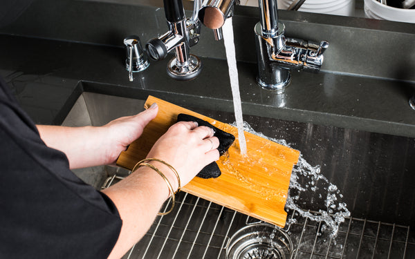 washing a bamboo board with hot water and soap