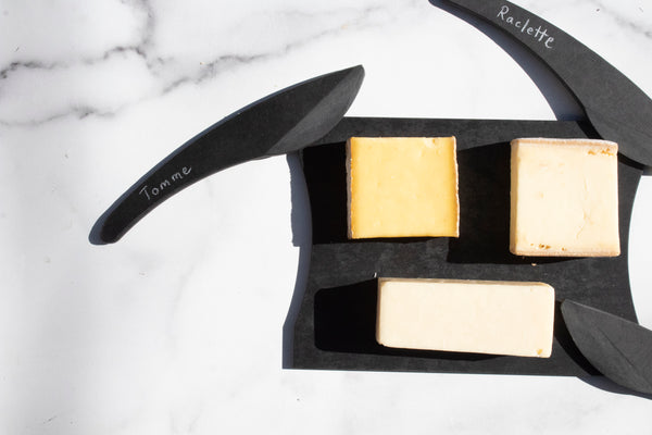 black cheese board and cheese knives