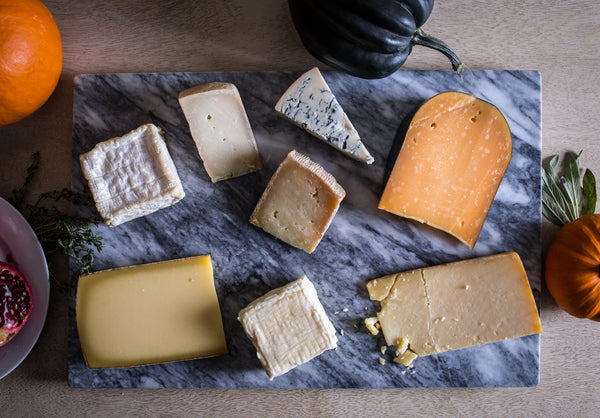 different kinds of cheese on a marble cheese board