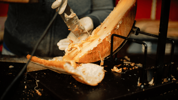 melted raclette being scraped onto bread