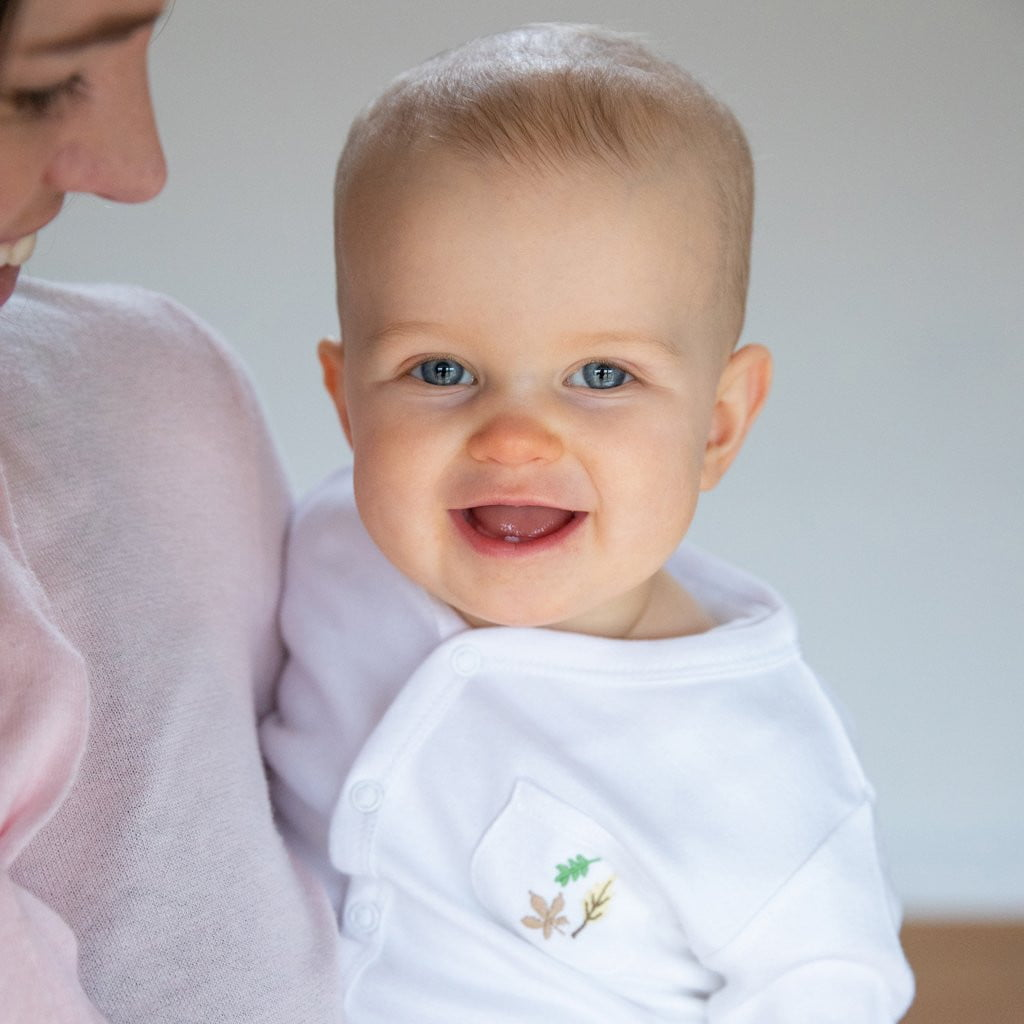 Baby smiling in baby sleepsuit