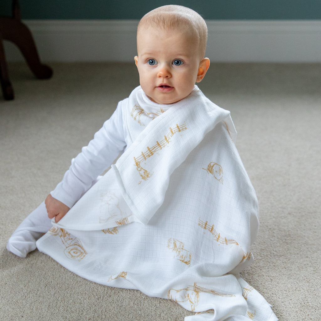 Image of baby sitting with Farm muslin square over shoulder