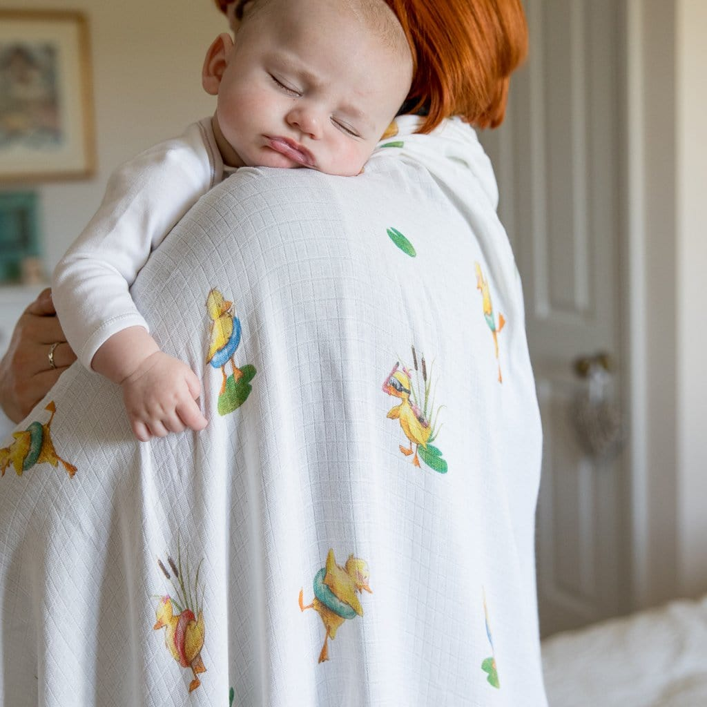 baby sleeping on mummy with duckling swaddle blanket