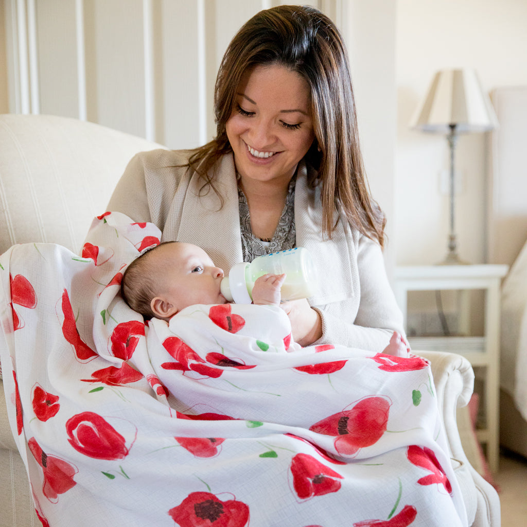 image of mummy feeding baby with a bottle on poppy swaddle blanket