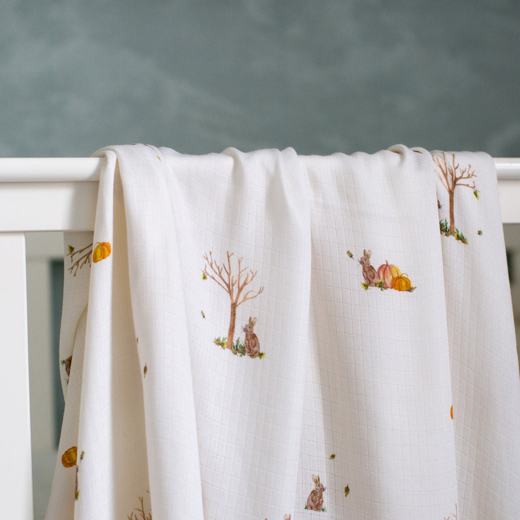 Bamboo swaddle blankets hanging on cot