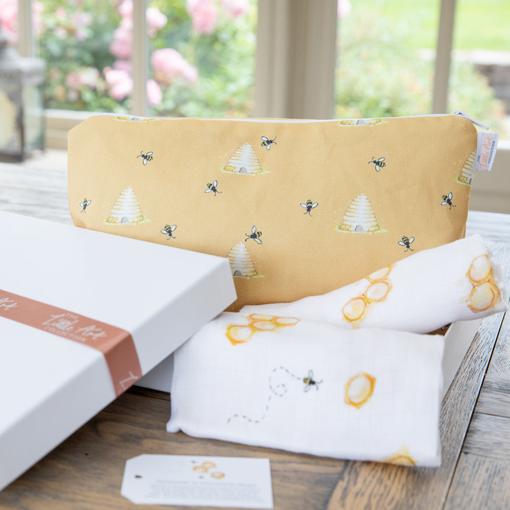 Image of nappy changing pouch, muslin squares and gift box on a table