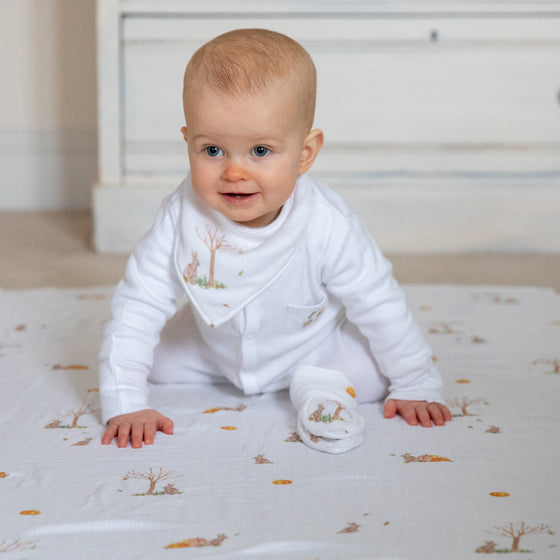 Image of baby in Rabbit dribble bib with teether and baby muslin