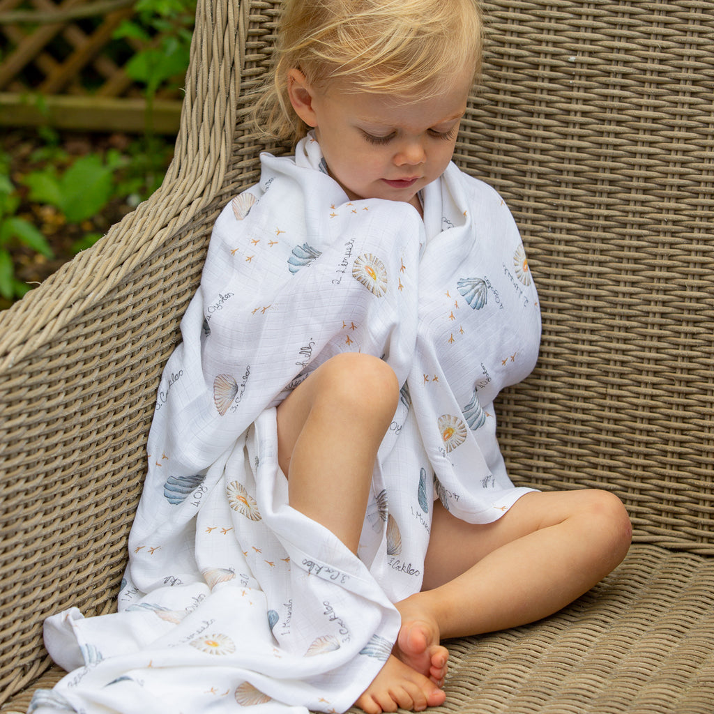 Image of toddler wrapped in Seashells swaddle blanket