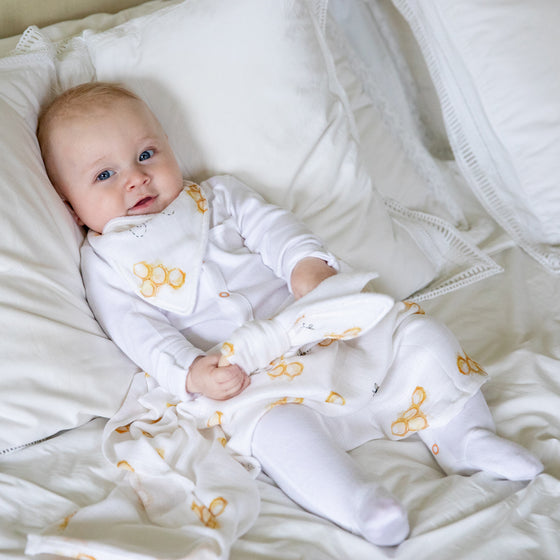Image of baby on bed with teether, dribble bib and baby muslin