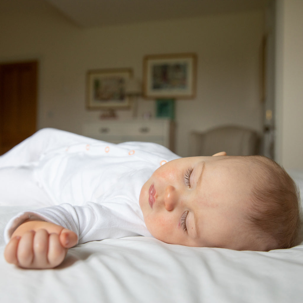 Image of baby sleeping in baby sleepsuit