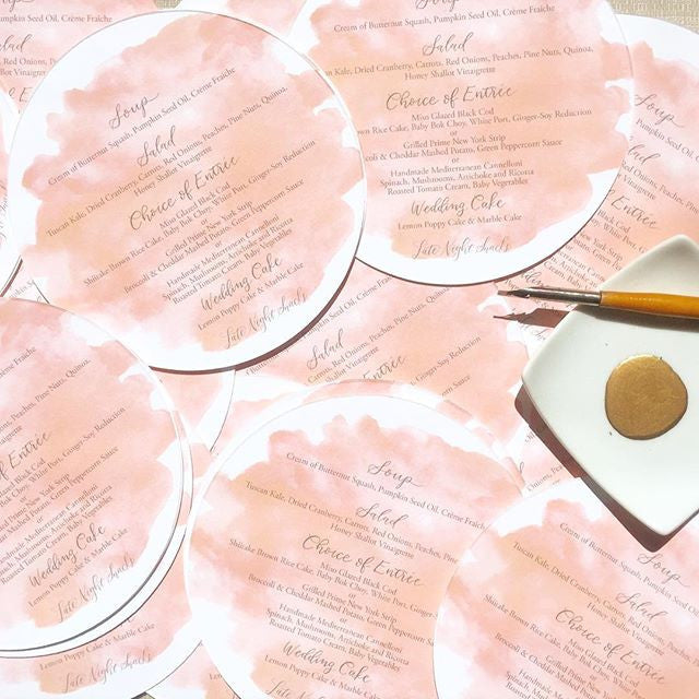circle die cut wedding menus with pink watercolor and gold calligraphy for destination wedding