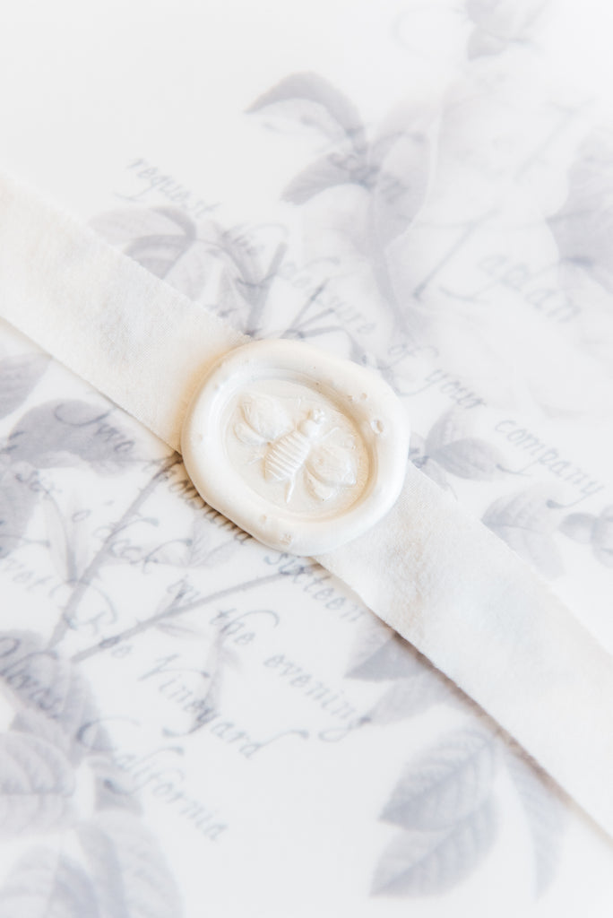 white wax seal with bee design