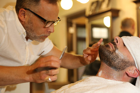 Mr. Natty performing a beard trim with a straight razor