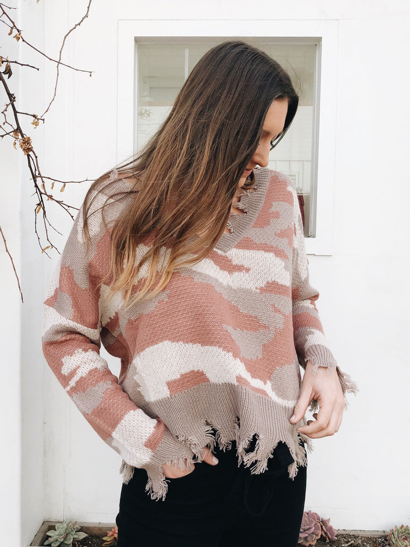 They can't miss you in this mauve camo sweater featuring distressed v-neckline and hem.