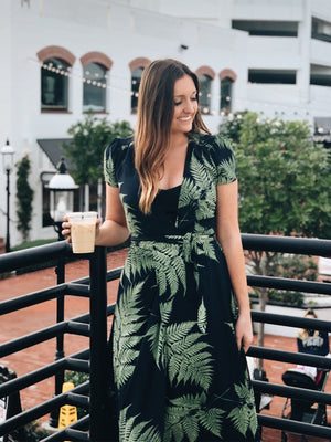 This maxi wrap dress features green on navy leaf design and a deep v neckline.