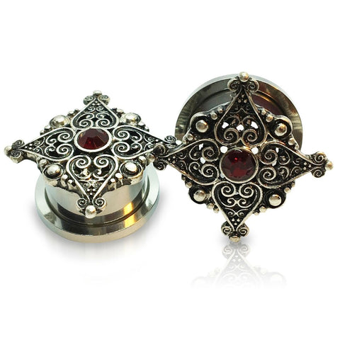 A pair of steel filigree plugs for stretched ears with a crimson gem inlay