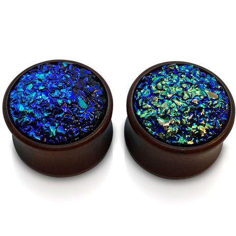 A pair of wood plugs for stretched ears with a faux druzy inlay