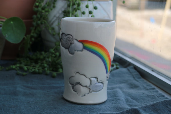 Cup with clouds and rainbows