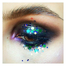 Product photo of multi-coloured green and purple chunky glitter being used as eye makeup