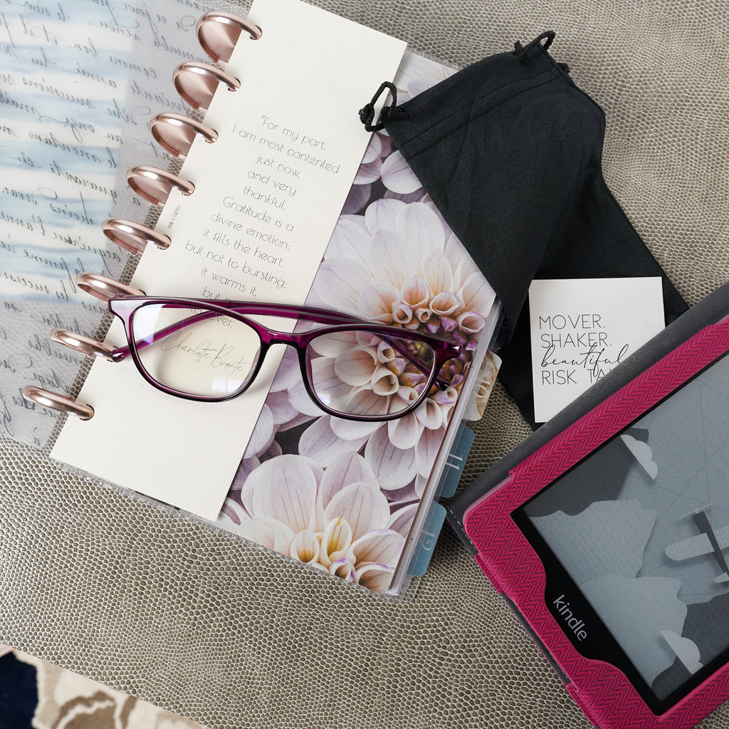 A pair of blue light glasses with a black cloth draw-string glasses case on a discbound planner from Jane's Agenda®.