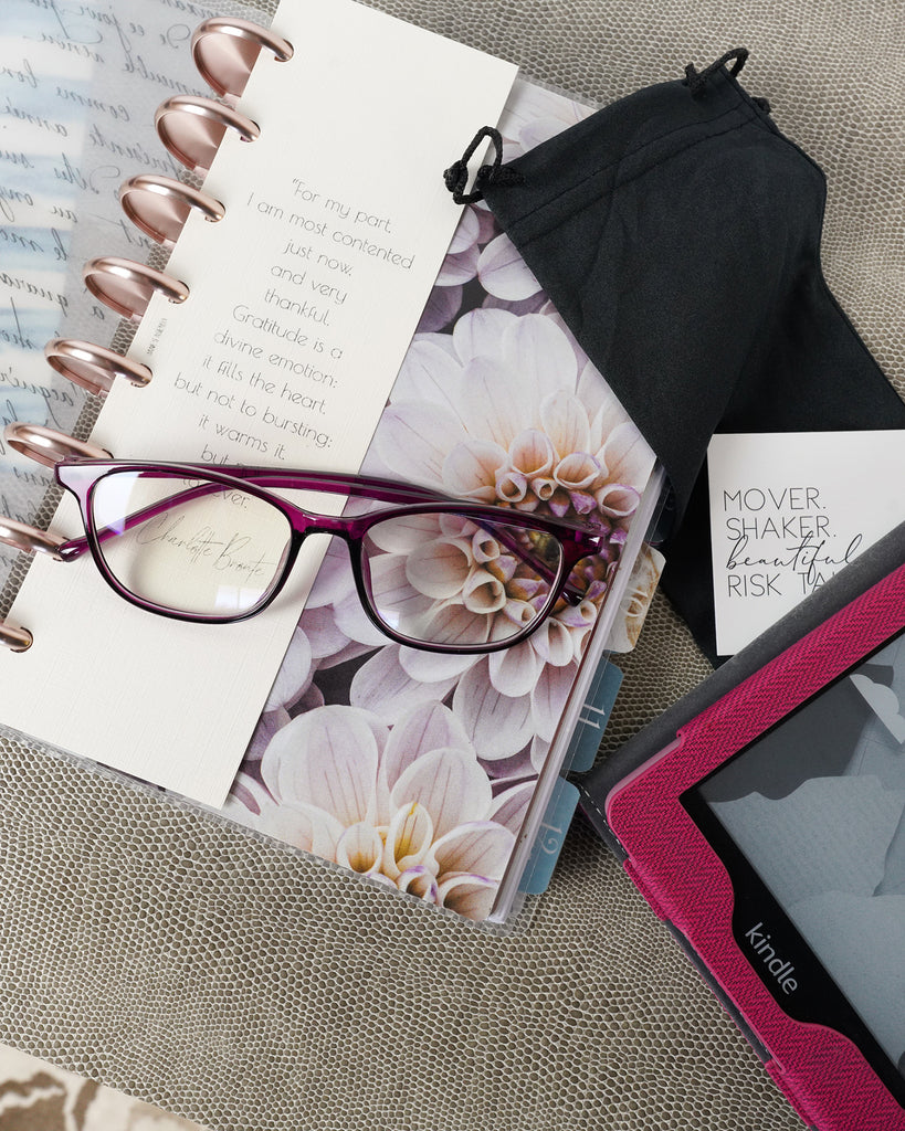 Burgundy framed blue light glasses with a black draw-string glasses case on a size six discbound planner from Jane's Agenda®.