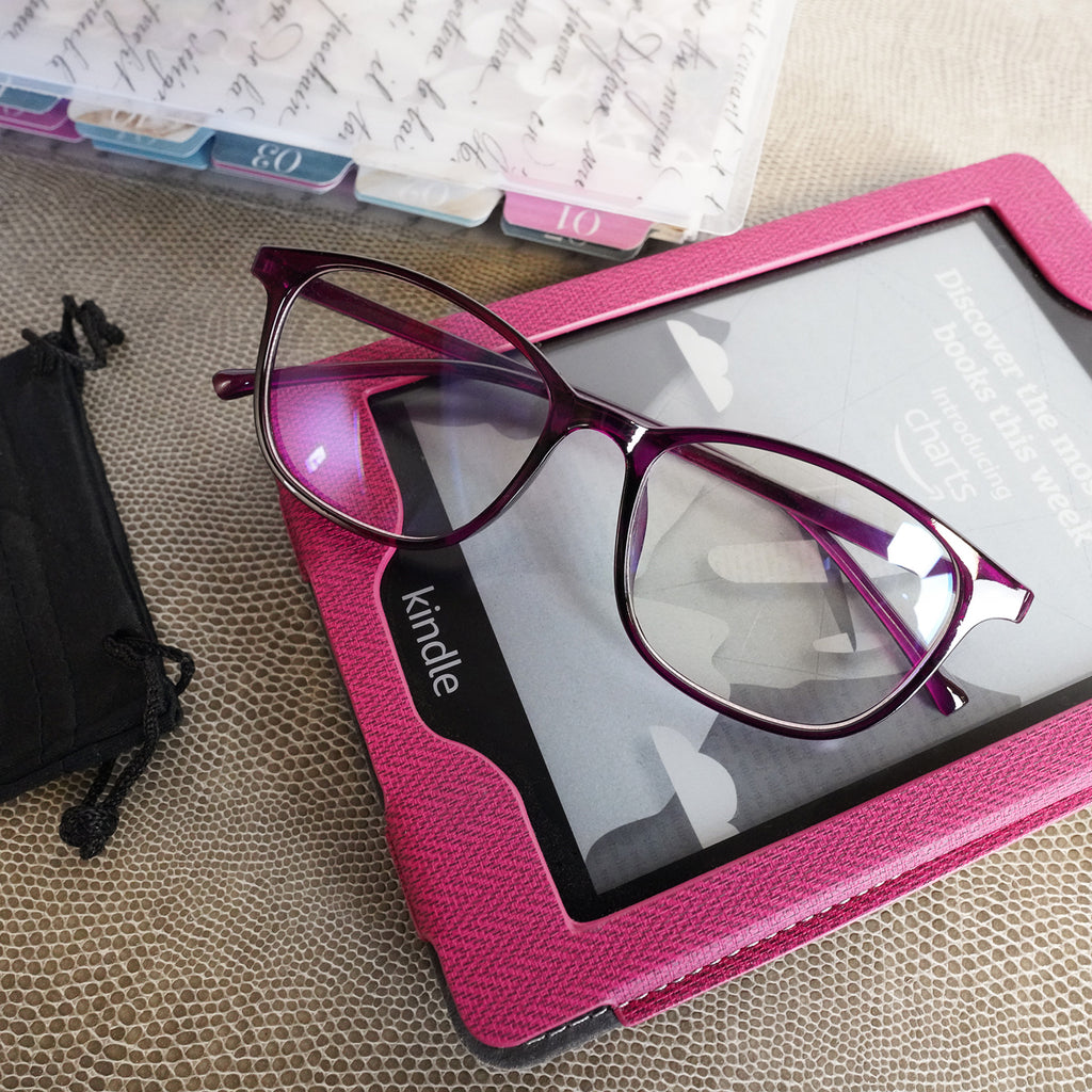 A pair of burgundy framed blue light glasses with a black draw-string glasses case from Jane's Agenda®.