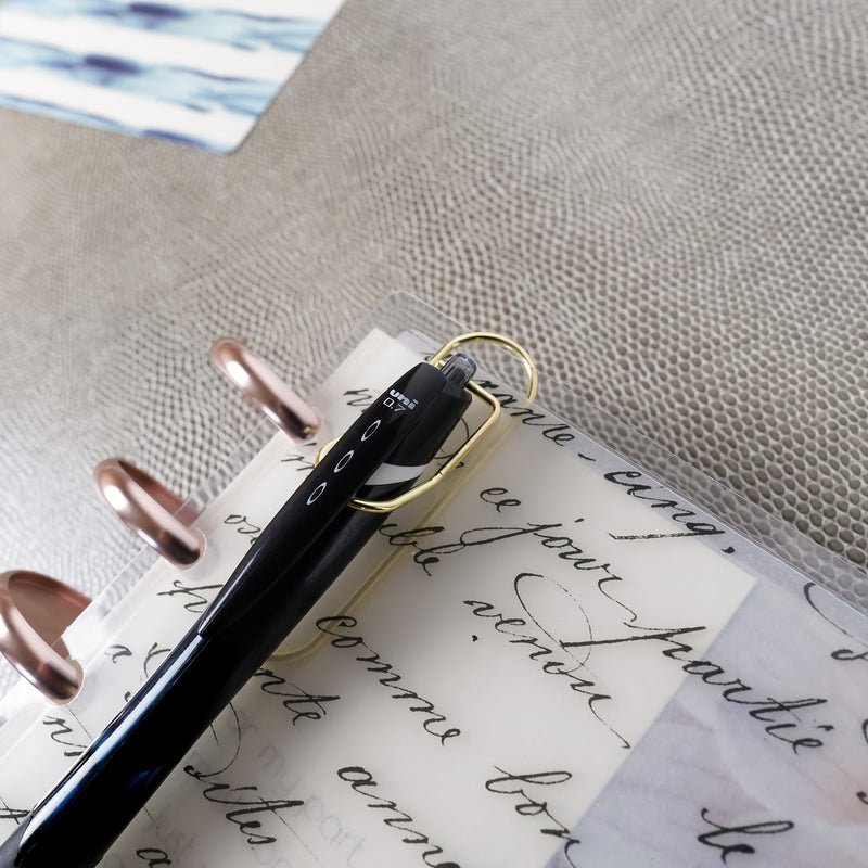 Gold Metal pen clip holding a Uni Jetstream Ball Point Pen on a French Handwriting discbound cover from Jane&